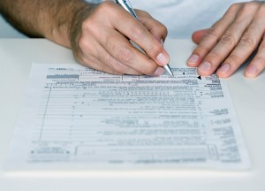 Man Filling out Tax Form